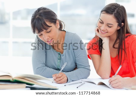 A smiling girls looks over into the work of her friend as they both study