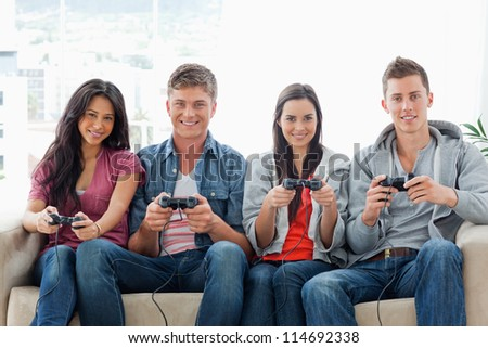 A smiling group of friends sit on the couch with controllers playing a game together