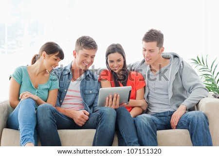 A smiling group sit around a tablet pc and watch the screen while on the couch - stock photo