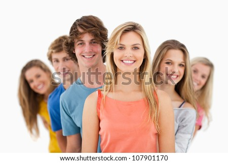 A smiling group standing behind one another at varied angles - stock photo