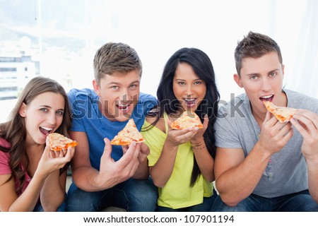 A smiling group with mouths open about to eat pizza as they look at the camera - stock photo