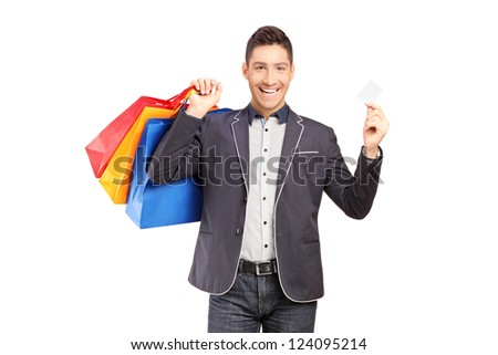 A smiling guy holding shopping bags and credit card isolated on white background - stock photo