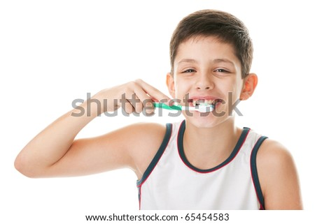 A smiling handsome boy is brushing his teeth; isolated on the white background - stock photo