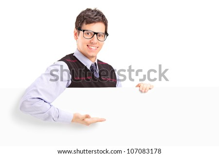 A smiling handsome guy gesturing on a white panel isolated on white background - stock photo