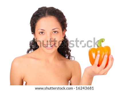 A smiling, happy woman holds a yellow pepper in her hand, standing on white background.