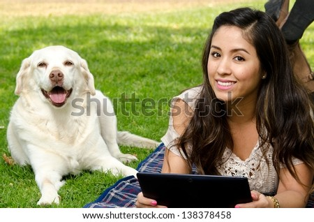 a smiling Hispanic woman in the park with her pet dog and holding a tablet.