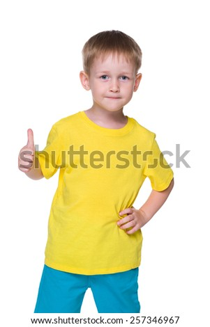 A smiling little boy holds his thumb up on the white background