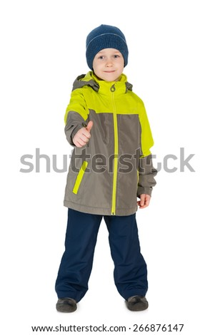 A smiling little boy in a jacket holds his thumb up against the white background