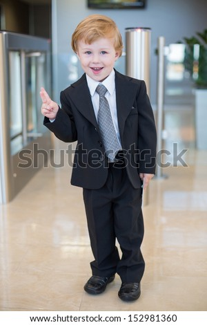 A smiling little boy in a suit at the entrance to the business center make victory gesture by two fingers - stock photo