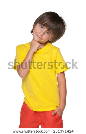 A smiling little boy in a yellow shirt stands against the white background - stock photo