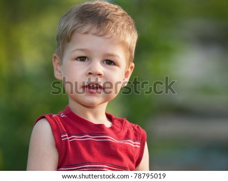 A smiling little boy is standing outdoors - stock photo
