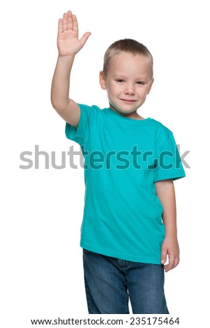 A smiling little boy stretching his right hand up on the white background - stock photo