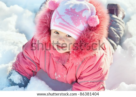 A smiling little girl in pink is lying in the snow