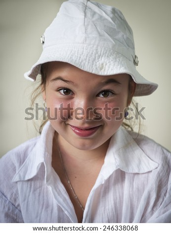 A smiling little girl in white panama.  - stock photo