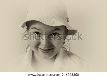 A smiling little girl in white panama. Vintage style. - stock photo
