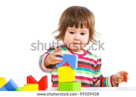 A smiling little girl is building a toy block. Isolated on white background - stock photo