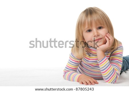 A smiling little girl is lying on the carpet; isolated on the white background