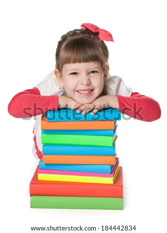 A smiling little girl is sitting on the floor near the pile of books on the white background