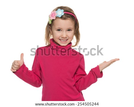 A smiling little girl makes a hands gesture against the white background - stock photo