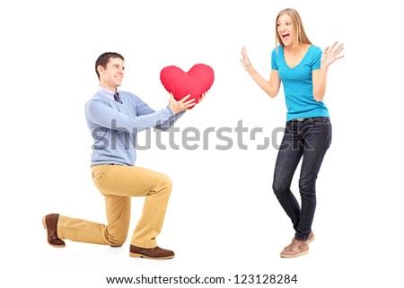 A smiling male kneeling with red heart and surprised woman isolated against white background - stock photo