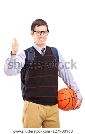 A smiling male student with school bag holding a basketball and giving thumb up isolated on white background - stock photo