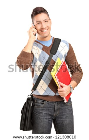 A smiling male student with shoulder bag and books talking on a cell phone isolated against white background - stock photo