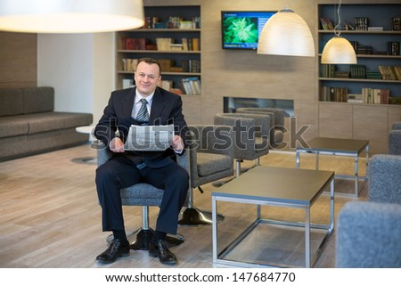 A smiling man in a suit and tie reading a newspaper