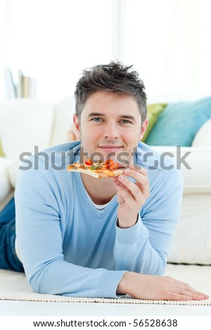 A smiling man lying on the ground and holding a pizza - stock photo