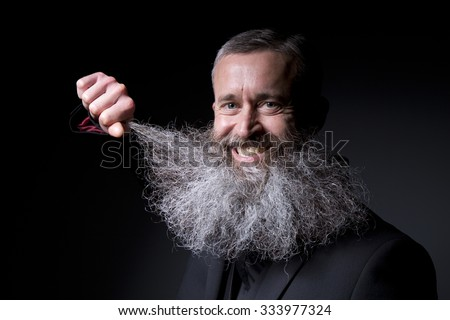 A smiling man plays with his huge grey beard on a black background