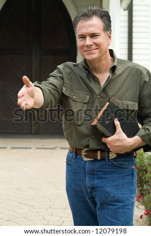 A smiling man standing in front of a church, holding a bible, with his hand extended in a welcoming gesture. - stock photo