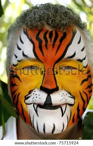 A smiling man who's face is painted like a tiger. - stock photo