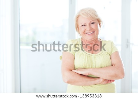 A smiling mature adult woman in her living room. - stock photo