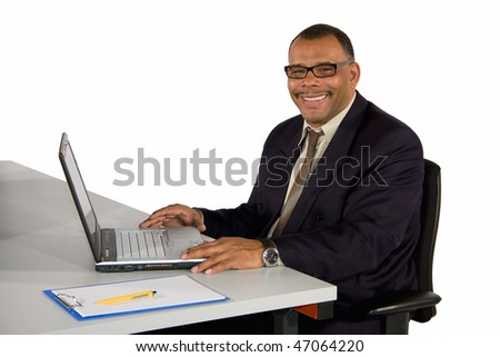 a smiling mature African-American businessman sitting in his office in front of his laptop, isolated on white background