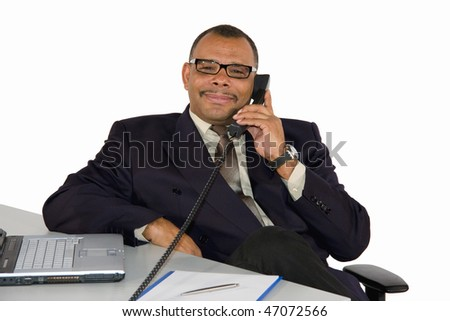 a smiling mature African-American successful businessman with a telephone and a laptop, isolated on white background