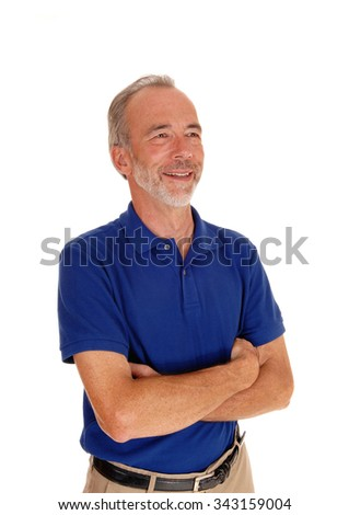 A smiling middle aged man standing isolated for white background in ablue t-shirt with his arms grossed. - stock photo