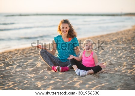 A smiling mother and daughter are sitting together on the beach, wearing workout gear. The sun is setting, they've gone for a nice run, and they are relaxing and happy, sitting in lotus position. - stock photo