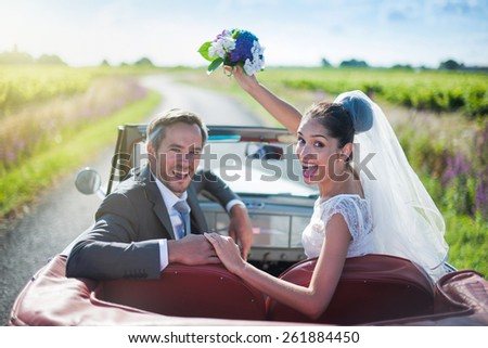 A smiling newlywed couple is holding hands and looking at camera in a retro car. the bride throws her bouquet - stock photo