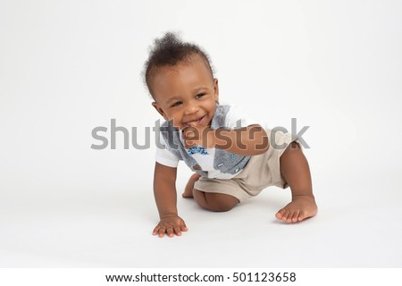 A smiling, nine month old, baby boy sitting on a white, seamless background with his finger in his mouth.