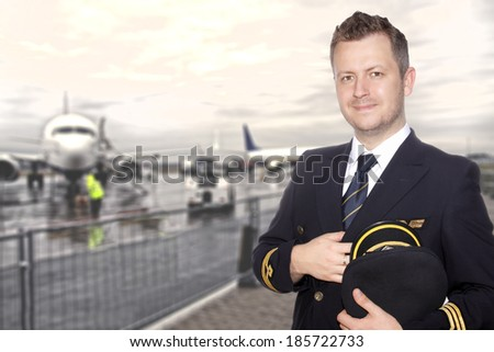 A smiling pilot in uniform on the tarmac