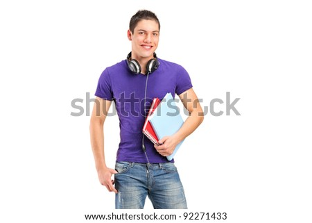 A smiling school boy with headphones holding books isolated on white background