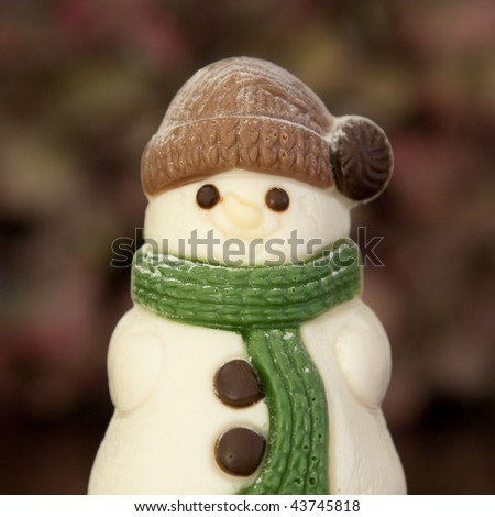 A smiling snowman with green scarf and brown hat. Made of chocolate. - stock photo