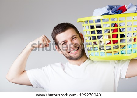 A smiling strong handsome man doing the laundry - stock photo