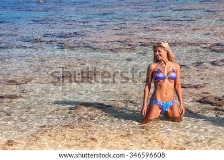 A smiling swimwear model posing in very clear shallow water - stock photo