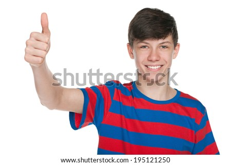 A smiling teen boy holds his thumb against the white background - stock photo