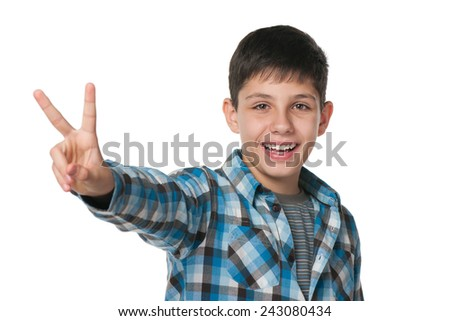 A smiling teen boy shows victory sign against the white background - stock photo