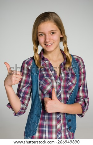 A smiling teen girl holds her thumbs up against the gray background - stock photo
