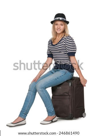 A smiling teen girl is sitting on a suitcase