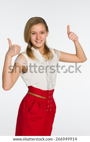 A smiling teen girl with her thumbs up against the gray background - stock photo