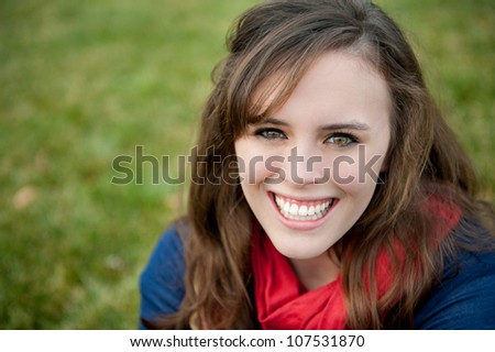 A smiling teenage girl outside on the grass - stock photo