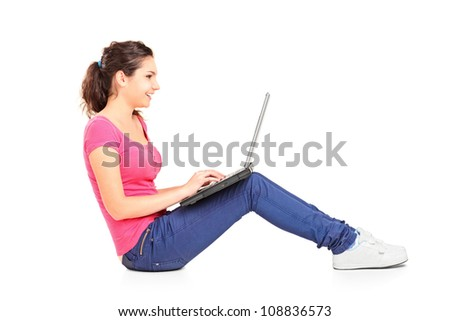 A smiling teenager doing her homework on a laptop isolated on white background
